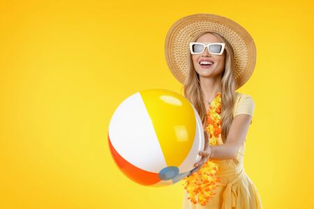 Attractive woman with beach accessories holding colorful ball on yellow background
