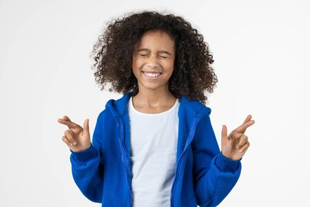 Cheerful little african girl holding fingers crossed for good luck standing isolated over white background