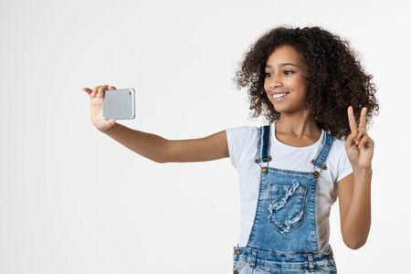 Cheerful young african girl kid à l'aide de téléphone mobile en tenant selfie montrant le geste de paix posant isolé sur fond blanc