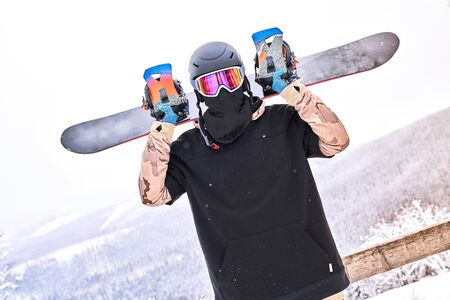Man snowboarder standing on the snowy hillside, holding snowboard behind his back and looking at camera near wood fence