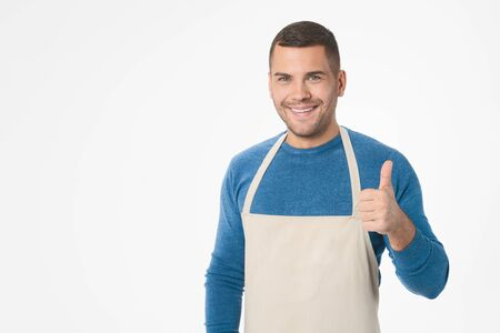 Young handsome shopkeeper man wearing apron doing thumb up gesture standing over isolated white background