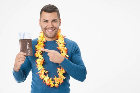 Young smiling man pointing on passport with tickets posing isolated on white wall background