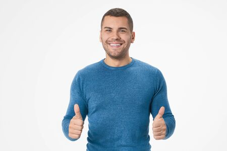 Portrait of cheerful man smiling and showing thumbs up isolated over white background