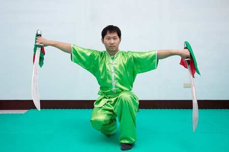 Man in green practice martial art in Chinese Martial Arts school.Kung fu