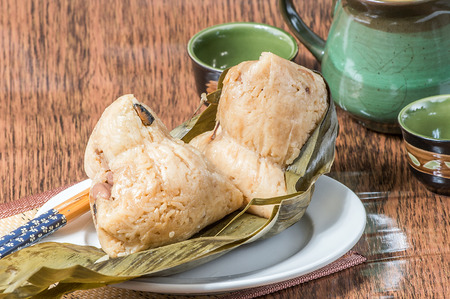 chinese meal: Zongzi or sticky rice dumpling (Chinese Rice Dumplings food) with teapot for dragon boat festival Stock Photo