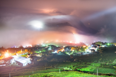 pour feliciter: dark night epic scene with colorful light over the city hidden in a fog Stock Photo