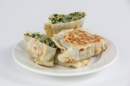 pan-fried leek dumplings on a plate isolated on white background