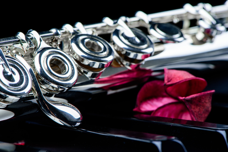 Jazz music instrument flute close up with flower isolated on black background Stock Photo