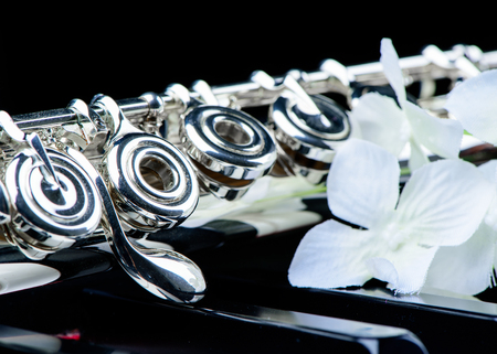 middle joint: Jazz music instrument flute close up with flower isolated on black background Stock Photo