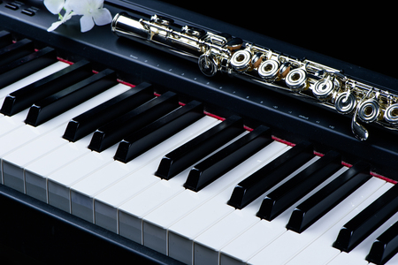 Jazz music instrument flute and piano keyboard close up with flower isolated on black background