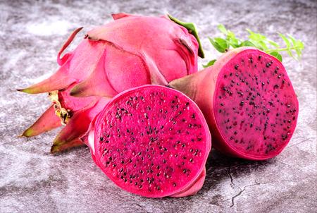 Beautiful fresh red dragon fruit (pitaya) on stone background