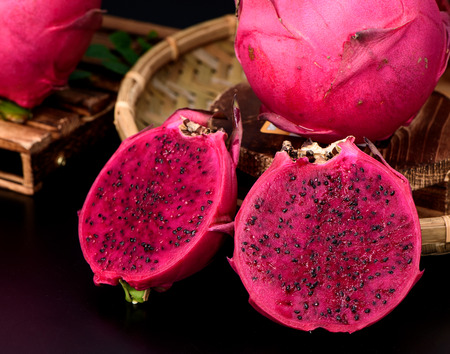 Dragon fruit (Pitaya) cut in half with a bamboo basket on black background