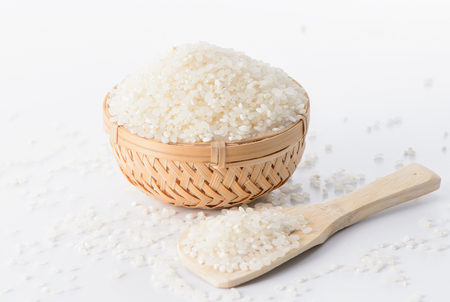Raw rice in a bamboo basket with a rice spoon isolated on white background