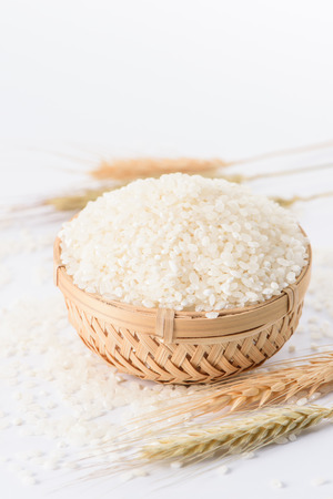 processed grains: Raw rice in a bamboo basket with wheat isolated on white background