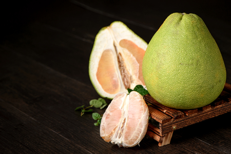fresh grapefruit, peeled grapefruit and grapefruit with slices on wooden table isolated on black background