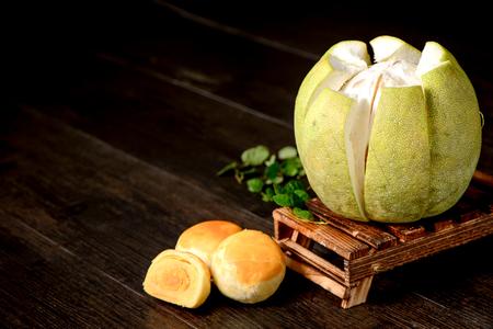 卵黄焼き菓子 (卵卵黄ショート ケーキ) や黒の背景に分離された木製のテーブルの上の皮をむいたグレープ フルーツ