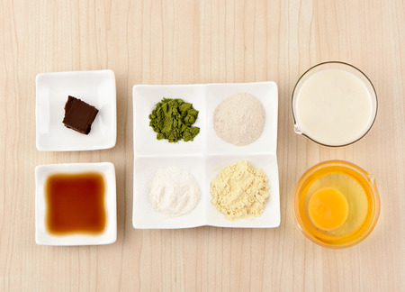 clutter: Ingredients of moon cake and mung bean pastry on a wooden table, from a top view.