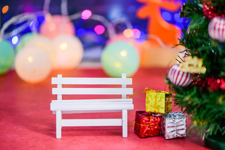 An empty white long bench with christmas tree on bokeh light Stock Photo
