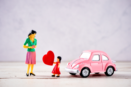 Taiwan, Tainan - April 17, 2018: Miniature people: A mother who is given a heart in love by little child girl with little bettle pink car, the concept of Mother's Day, blank background for text, macro shot Editorial