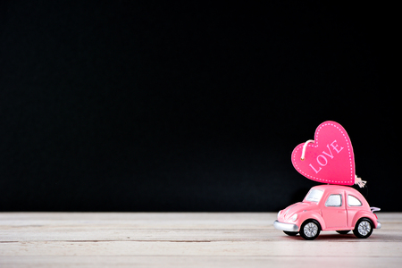 Taiwan, Tainan - April 17, 2018: Little beetle pink car carries a heart with love in blank background for text, Valentine's Day concept, Mother's Day concept, macro shot. Sajtókép