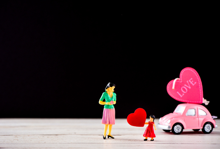 Taiwan, Tainan - April 17, 2018: Miniature people: A mother who is given a heart in love by little child girl with little bettle pink car, the concept of Mothers Day, blank background for text, macro shot