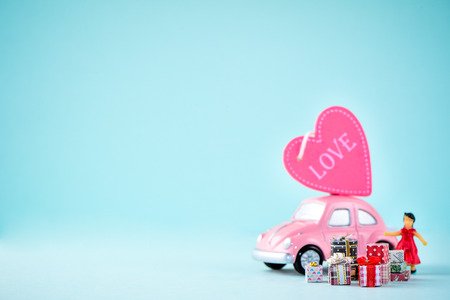 Taiwan, Tainan - April 17, 2018: Miniature people: A mother who is given a heart in love and gifts by little child girl with little bettle pink car, the concept of Mother's Day, blank background for text, macro shot