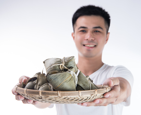 A man is giving zongzi or rice dumpling to others as a present or souvenir on Dragon Boat Festival, Asian traditional food, white background
