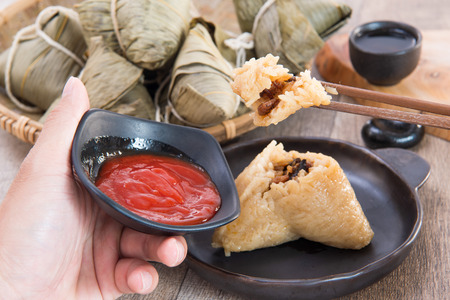 A man is going to eat zongzi or rice dumpling on Dragon Boat Festival, Asian traditional food Stock Photo