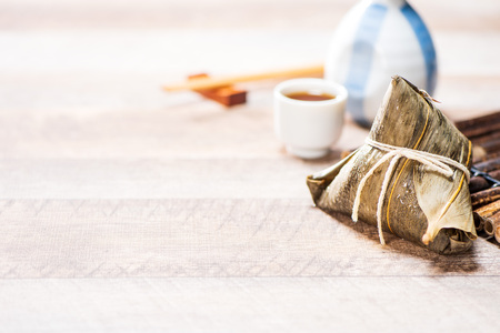 Zongzi(rice dumpling) with a cup of tea on a wood table, Dragon Boat Festival, Asian traditional food, Chinese