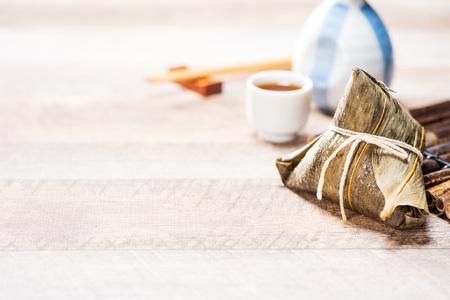 zongzi(粽子)用一杯茶在木桌,船舶节日,亚洲传统食品,中文