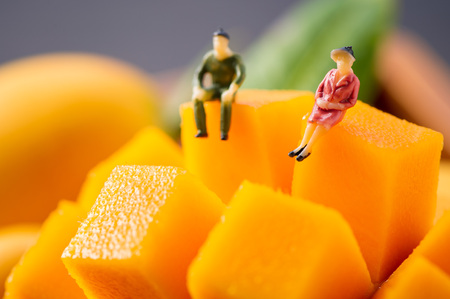 Miniature people: A man and a woman sit aside but on a different mango rock, and look into the distance and lost in thought, the concept of a married couple are thinking about their life.