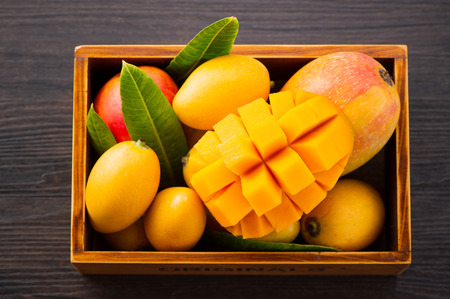 Fresh and beautiful mango fruit set in a wooden box with sliced ??diced mango chunks on a dark wooden background, copy space(text space), blank for text Stock Photo