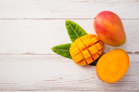 Fresh and beautiful mango fruit with sliced ??diced mango chunks on a light wooden background, copy space(text space), blank for text, top view. Banque d'images