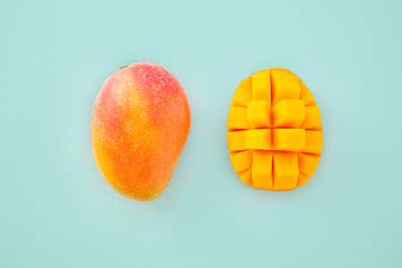 Fresh and beautiful mango fruit with sliced ??diced mango chunks on a light blue background, copy space(text space), blank for text, top view.