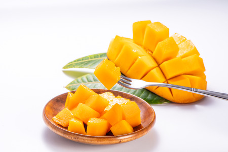 Fresh and beautiful mango in a wooden plate with sliced ??diced mango chunks isolated with white background, copy space(text space), blank for text Stock Photo