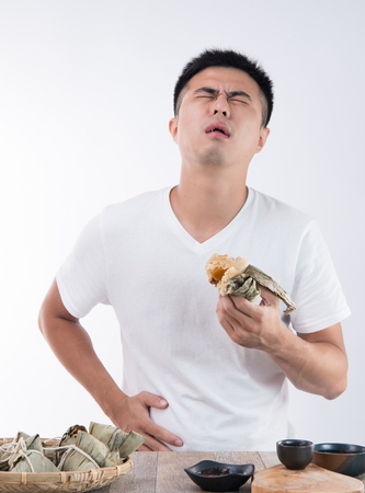A man has a stomachache after eating delicious zongzi(rice dumpling) on ??Dragon Boat Festival, Asian traditional food, white background