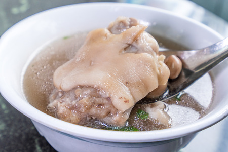 Taiwans distinctive famous snacks: Peanut pork knuckle(pigs trotter) soup in a white bowl on stone table, Taiwan Delicacies, Taiwan Street Food