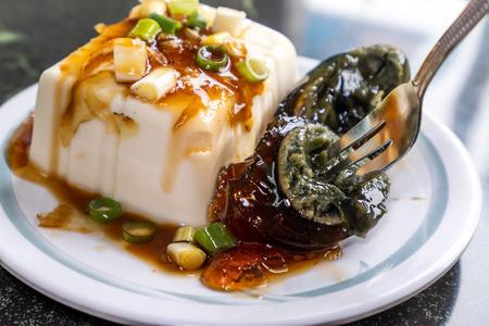 Taiwan's distinctive famous snacks: thousand-year-old eggs tofu(pidan tofu) in a white plate on stone table, Taiwan Delicacies, Taiwan Street Food 写真素材