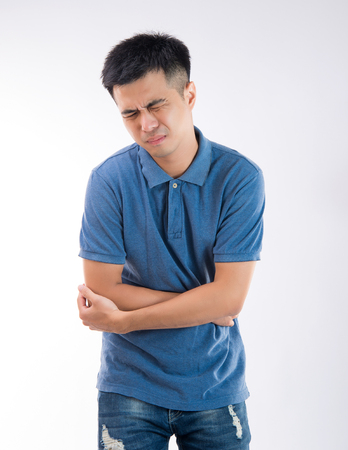 Man putting his hands for belly or stomach ache on white background 免版税图像