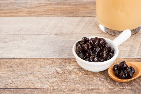 Tapioca Pearl , Bubble topping for tea or other beverage, in a cup, place on wooden table. Copy space Stock fotó
