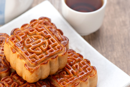 Mooncake in chinese traditional mid-autumn festival(moon festival) on wooden table background with copy space(text space) and table setting, close up.