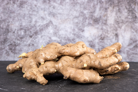 Whole ginger roots on dark old stone background table, space for text.