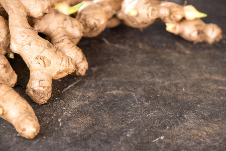 Whole ginger roots on dark old stone background table top view space for text.