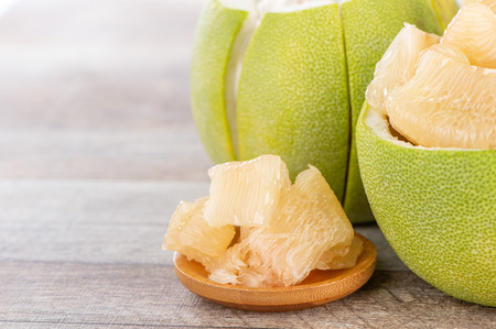fresh and peeled pomelo(shaddock), grapefruit with slices on wooden table background