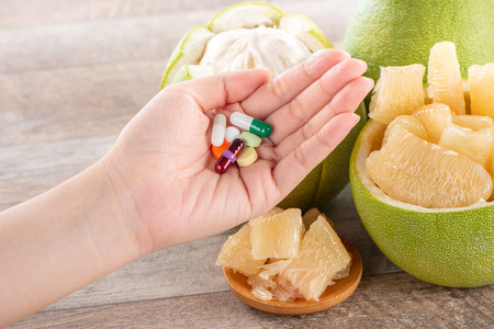 fresh and peeled pomelo(shaddock), grapefruit with drug, concept of drug interatcions Stock Photo