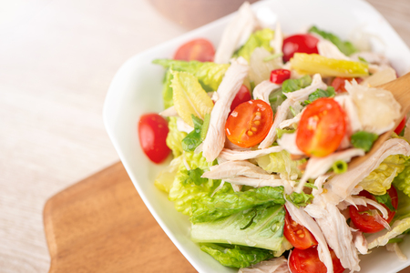 Fresh and delicious homemade chicken salad with tomatoes and pomelos in wooden background, concept of healthy and diet, top view, copy space Archivio Fotografico
