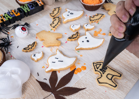Fresh homemade decorating halloween dessert with ghost, creeping spider, bat, haunted castle and horrifying eyeball on wooden background, copy space Stock Photo