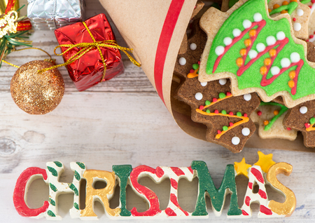 Tasty and cute baked Christmas cookies (gingerbread) with beautiful xmas decoration in paper bag on light wooden table background, close up, copy space (text space)