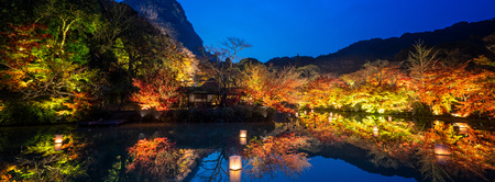 Beautiful Japanese garden named Mifuneyama Rakuen in autumn night view with maple leaves and lake reflection. Editorial