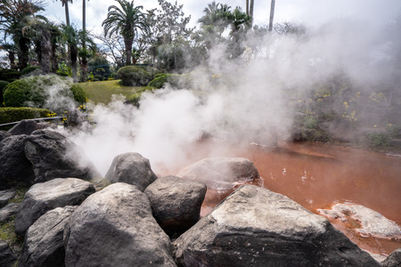 Red hot spring near UMI JIGOKU (Sea Hell) pond in autumn, which is one of the famous natural hot springs viewpoint, the japanese in picture means Stock Photo